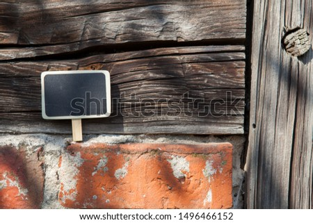 An information sign stands on a brick and wooden obsolete wall #1496466152