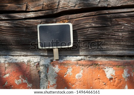 An information sign stands on a brick and wooden obsolete wall #1496466161