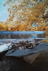 An Infrared Photography view of an abandoned boats by a lakeside surrounded by golden foliage trees.