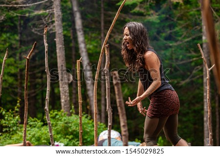 An inspirational caucasian woman is seen helping people through mindful yoga exercises during a woodland retreat, singing and shouting with room for copy.