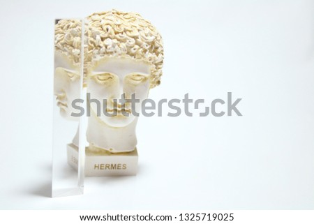 An installation consisting of Hermes statueand prism on white background.