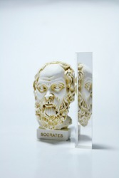 An installation consisting of Socrates statue, prism on white background.