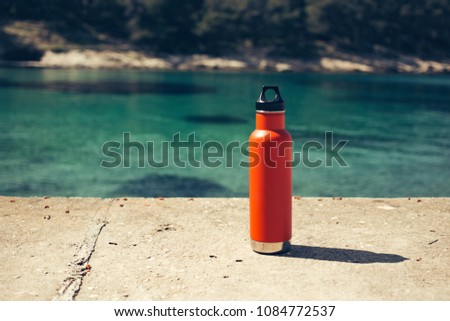 An insulated orange steel water bottle at the beach