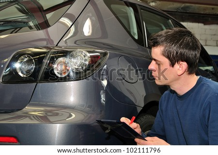 An insurance agent inspecting a car.