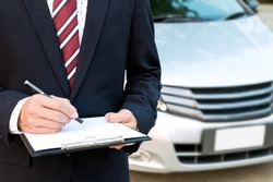 An insurance expert employee working with a car at the outdoor