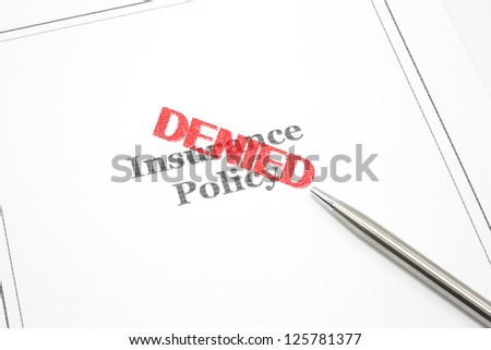 An insurance policy and a pen and the word Denied in red stamp across the policy.