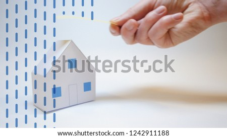 an insurer's hand protects a paper house from natural disasters, concept #1242911188