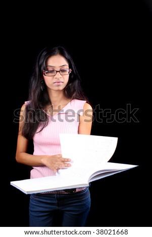 Indian teenage girl reading her notes, on black studio background ...