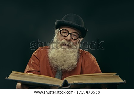 An intelligent old man in glasses and bowler with a long gray beard holds an old big book and looks at the camera. Old age wisdom. Foto stock ©