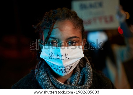 An intense look from an African-American woman demonstrating against racism. Demonstrators in a city with banners fighting for their rights, holding signs. Black Lives Matter. Photo stock ©