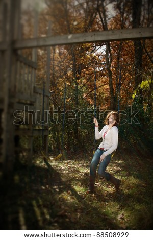An intentional blur/selective focus of a woman on a swing