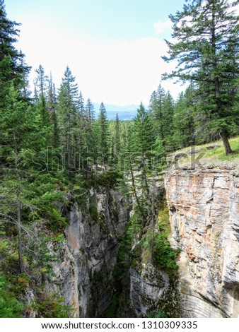 An interesting and unique view of Johnstone Canyon in Banff National Park, Alberta, Canada.  The canyon was caused by erosion of limestone rock. The picture shows the steep cliffs carved by the canyon