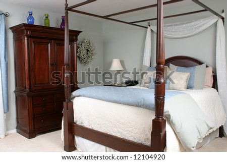 An interior of a master bedroom with a four poster bed and beautiful cherry wood furniture.