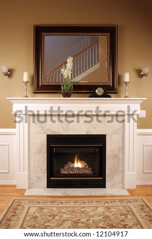 An interior shot of a marble fireplace with beautiful woodwork,a framed mirror and warm inviting colors.