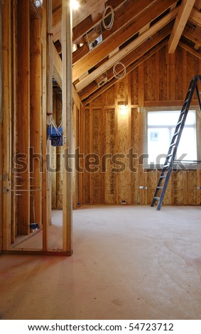 An interior view of a new home under construction with exposed wiring and and a ladder in place. Vertical shot. - stock photo