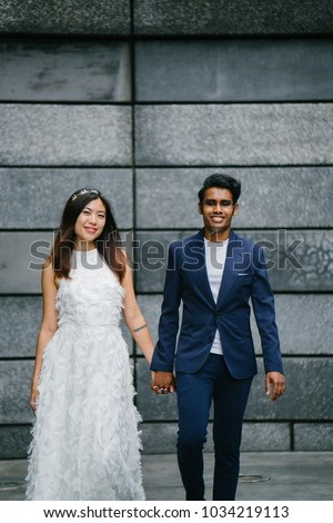 An interracial Asian couple (Indian man, Chinese woman) hold hands and take a portrait against a grey slate stone wall in the day. They are smiling and look happy and confident about their future.