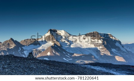 An inukshuk on a ridge with the sun rising on glaciers across the valley. Taken just off the icefields parkway, near the athabasca glacier, Jasper National Park, Alberta, Canada. #781220641