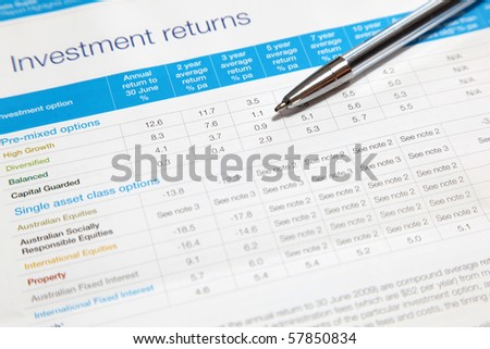 An investment returns statement with ball point pen. Note shallow depth of field, focus on ball point pen.