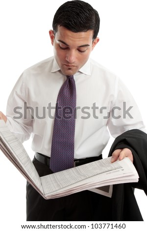 An investor, stockbroker or businessman reads the sharemarket pages of the financial newspaper