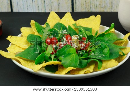 An inviting salad of corn chips, green salad leaves, red cherry tomatoes and green olives.  A sprinkling of Parmesan cheese completes the picture.
