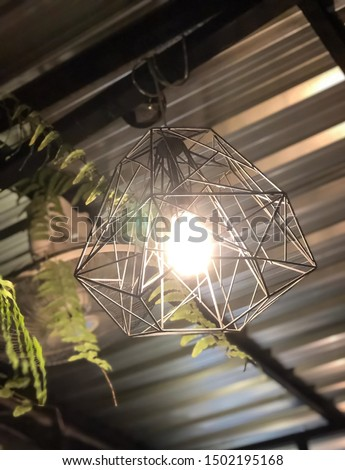 An iron cage with a light bulb inside and hanging on the ceiling to illuminate the house. #1502195168