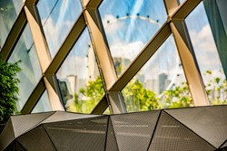 An irregular triangular shaped sculpture of honeycomb mesh, separates visitors from the glass-clad conservatory dome, Cloud Forest, Gardens by the Bay.The Singapore Flyer is visible in the background.
