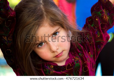 An irritated little girl gives an intense look.  She has her arms up and is leaning on something with her head cocked to the side, looking at the viewer with a furrowed brow and intense eyes. Stockfoto ©
