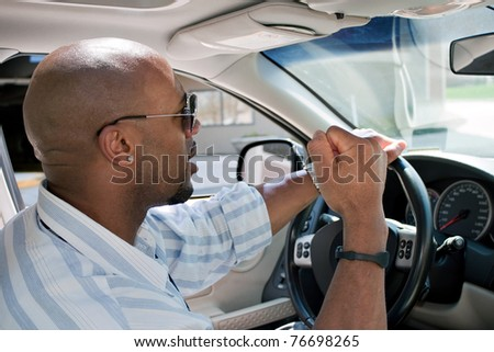 An irritated man driving a car is expressing his road rage with his fist clenched in the air. - stock photo