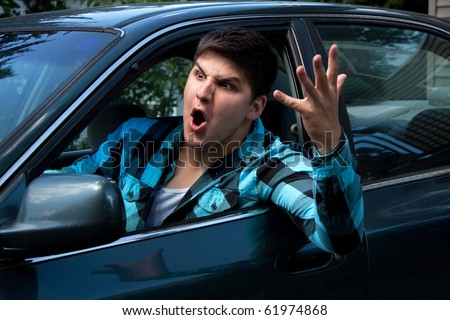 An irritated young man driving a vehicle is expressing his road rage.