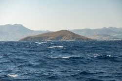 An island at Aegean Sea on a choppy waters with foggy land in the background.