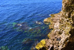 An island in the blue sea with a rocky broken coast and rare greenish grass. Multi-colored limestone rocks. Red-brown, beige and yellow rocky monoliths. Colorful transparent waves. Underwater flora.