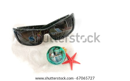 An isolated angled closeup view of a pair of sunglasses, christmas bulb, red star fish, on some white sand. Pool reflections in the Christmas bulb and sunglasses.
