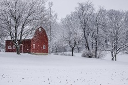 An isolated barn with snow falling