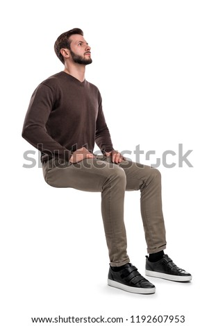 An isolated bearded man in casual wear sits on a white background with hands on his thighs and looks up. Searching for answers. Waiting for help. Thinking of problems.