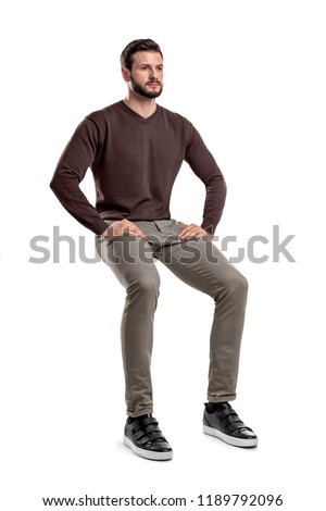 An isolated bearded man in casual wear sits on a white background with hands on his thighs. Sitting and waiting. Meditating. Neutral expression. #1189792096