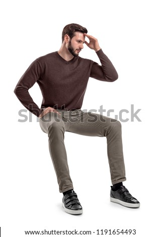 An isolated bearded man in casual wear sits on a white background with one hand touching his forehead. Thinking about troubles. Unresolved problems. Headache. #1191654493