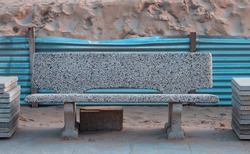 An isolated concrete bench in a construction site on the beach in front of a sand dune (Pesaro, Italy, Europe)