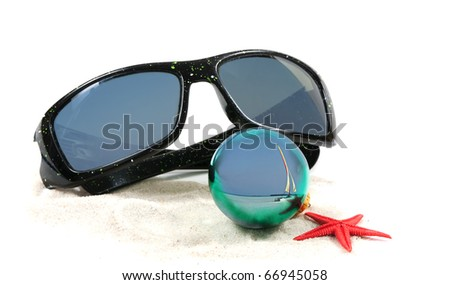 An isolated front view of a pair of sunglasses, christmas bulb, red star fish on some white sand. - stock photo