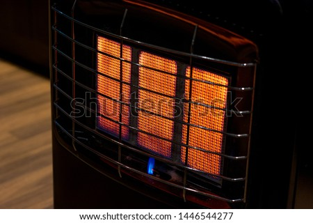 An isolated gas heater on a freezing cold winter night burning at full capacity, glowing orange and radiating heat.