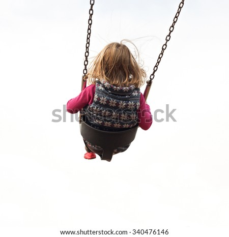 An isolated girl swinging high on a swing