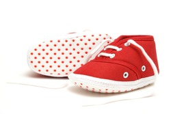 An isolated pair of red baby shoes for the newborn to wear.