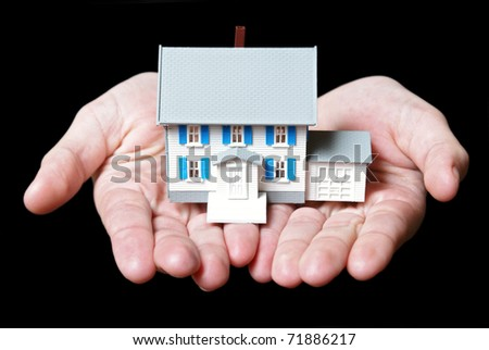 An isolated pair of womans hands holds a toy house.