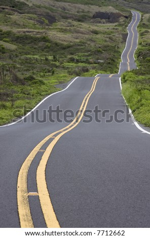 An isolated road winds through a green landscape. - stock photo