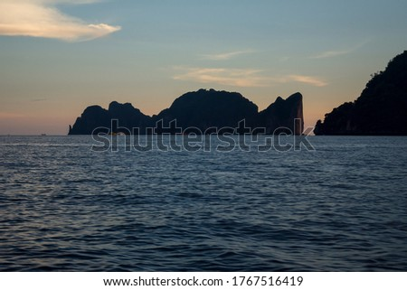 An isolated rocky tropical island of Ko Phi Phi Leh with high limestone cliffs and blue water of the Andaman Sea, seen at sunset golen hour from long-tail boat near Ko Phi Phi Don; Krabi, Thailand