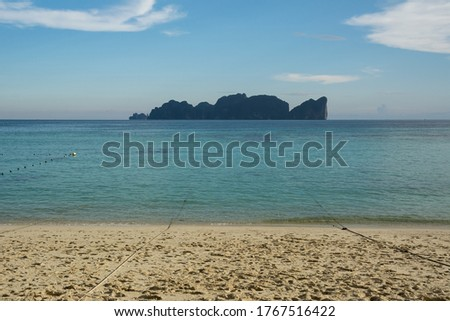 An isolated rocky tropical island of Ko Phi Phi Leh with high limestone cliffs and blue water of the Andaman Sea, seen at sunset from Long Beach on Ko Phi Phi Don, Krabi, Thailand