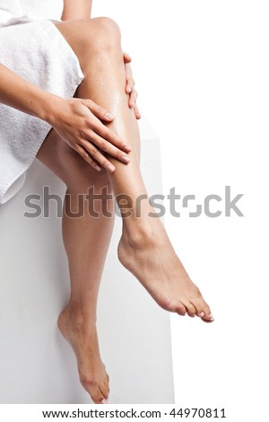 An isolated shot of a beautiful black woman applying  lotion on her legs