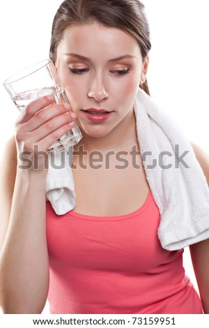 An isolated shot of a beautiful sporty caucasian woman holding a glass of water