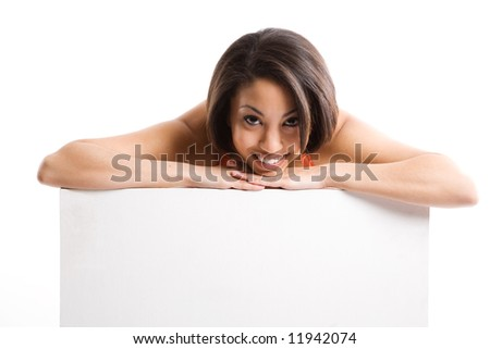 An isolated shot of a beautiful woman smiling and showing an empty billboard
