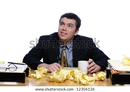 An isolated shot of a businessman sitting at desk, topped with crumpled yellow paper, looking up towards the ceiling/sky, with a bewilered expression.
