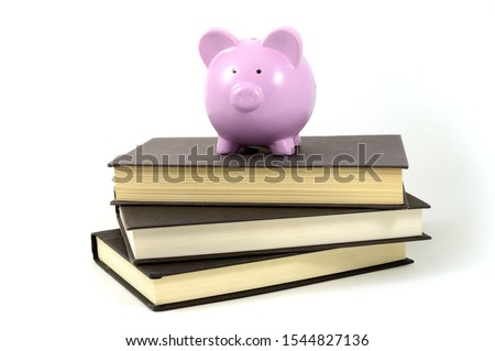 An isolated shot of a pig bank and books to illustrate school savings funds. #1544827136